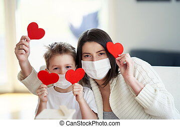 Mother and son at home quarantine during coronavirus pandemic holding hearts