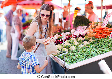 Mother and son at market - Mother and son buying green peas...