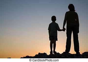 Silhouettes of mother and son at sunset.