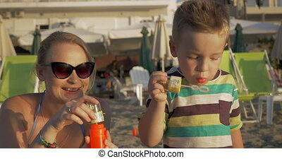 Mother and Son Blowing Soap Bubbles on the Beach