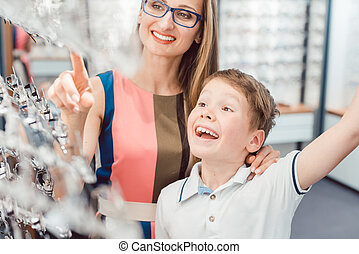 Mother and son both liking the eyeglasses offered in optician shop
