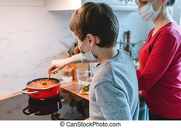 Mother and son cooking at home together wearing masks