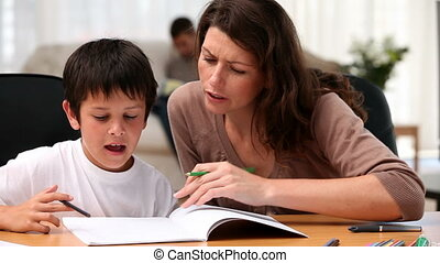 Mother and son doing homework sitting at a table in the living room