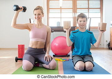 Mother and son doing weight training at home during lockdown curfew