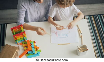 High angle view of mother and son drawing picture then colouring it with pencils at table at home bonding and enjoying time together. Childhood and hobby concept.