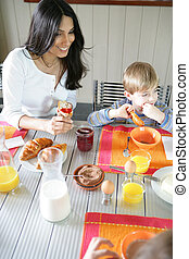 Mother and son eating breakfast at the table