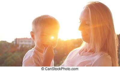Mother and son eating strawberries at sunset. Happy family concept.