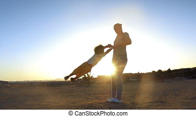 Slow motion of a mother spinning the son around on the beach against bright evening sunlight. Happy family vacation
