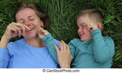 Mother and son fooling around lying on the grass. Laughing,...