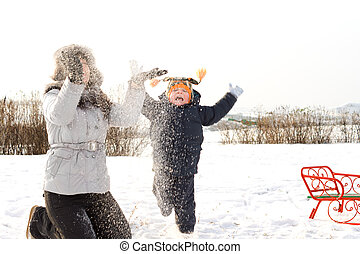 Mother and son frolicking in the snow
