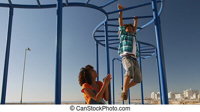 Mother and son having fun at playground - Low angle front ...