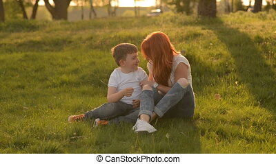 Mother and son having fun outdoors sitting on grass