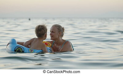 Mother and son having fun playing in the sea