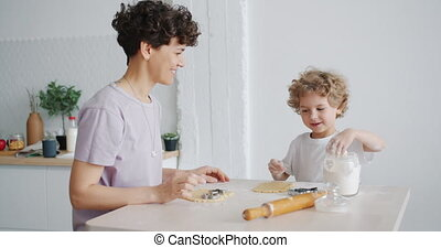 Mother and son having fun with flour cooking home-made...