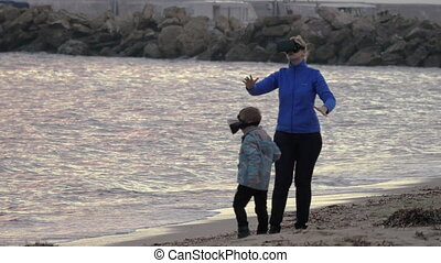 Mother and son having fun with VR glasses on the shore