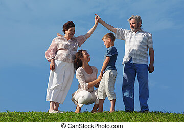 mother and son holding for hands, grandparents making house roof gesture, summer lawn