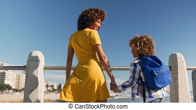 Mother and son holding hands at beach