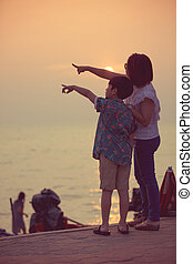 Mother and son in a deep moment of love during sunset at beach