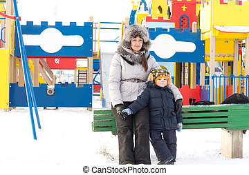Mother and son in a snowy childrens playground