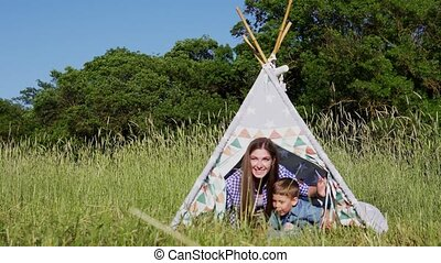 mother and son in a tent in the Woods on a picnic