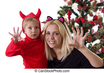 Mother and son in deuce costumes under Christmas tree