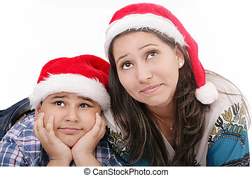 Mother and son in Santa hats smiling and looking up