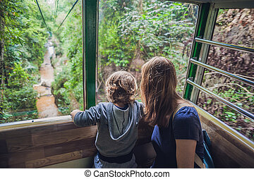 Mother and son in ski lift cabin in summer Over the waterfall. Passengers on a cable car