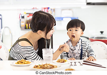 Mother and son in the kitchen, eating noodles together