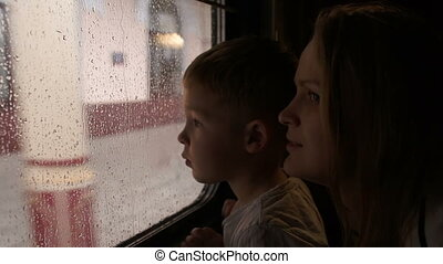 Mother and son in the train looking out the window on a rainy day