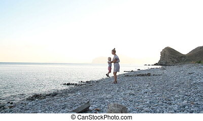 Mother and son is walking along the beach