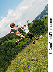 mother and son jumping in meadow