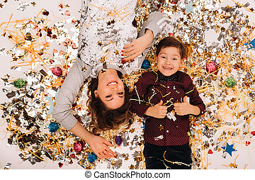 mother and son lie on the floor in confetti on a white background. A woman and a boy in confetti on a white background