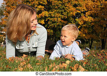 mother and son lie on the grass at the park in autumn