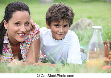 Mother and son lying in the grass
