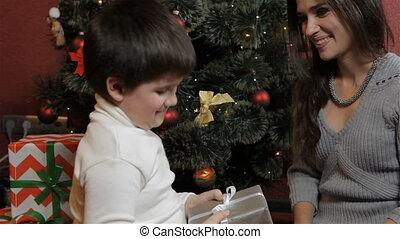 Mother and son make eskimo kiss near the christmas tree