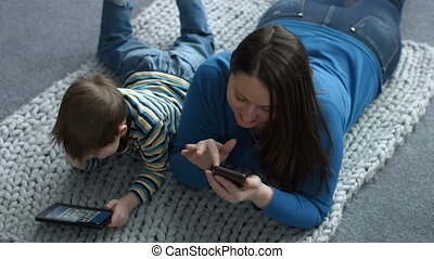 Mother and son networking with digital devices