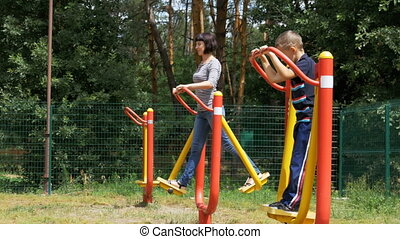 Mother and Son on Street Exercise Machines go in for Sports