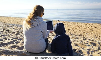 Mother and son on the beach with tablet PC