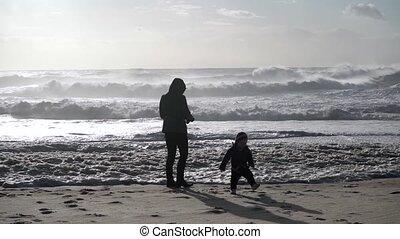 Mother and son on windy beach with big waves, Nazare, ...
