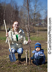 mother and son planting tree - mother and son with spade ...