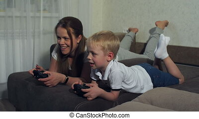Mother and son play computer games with joysticks lying on the couch.