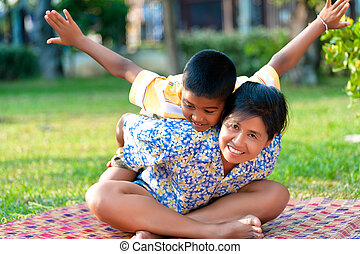 Mother and son play in a park