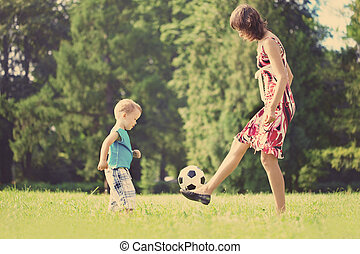 Mother and son playing ball in the park.