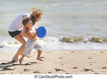 mother and son playing frisbee on beach