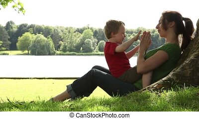 mother and son playing hand clap - mother and son playing a...