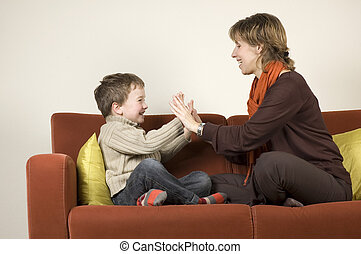 Mother And Son Playing On A Couch