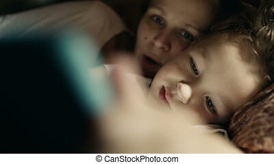 Mother and son playing on tablet PC before bed