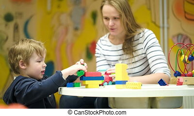 Mother and son playing together with toys