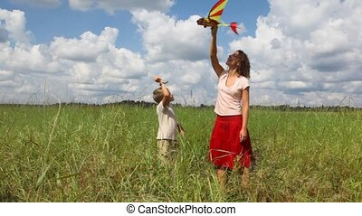 mother and son playing with airplane in the filed