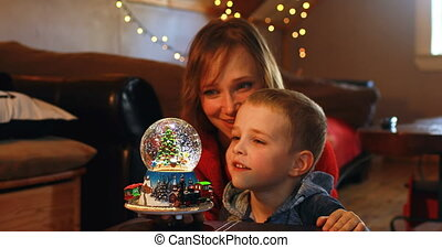 Mother and son playing with crystal ball toy during Christmas 4k